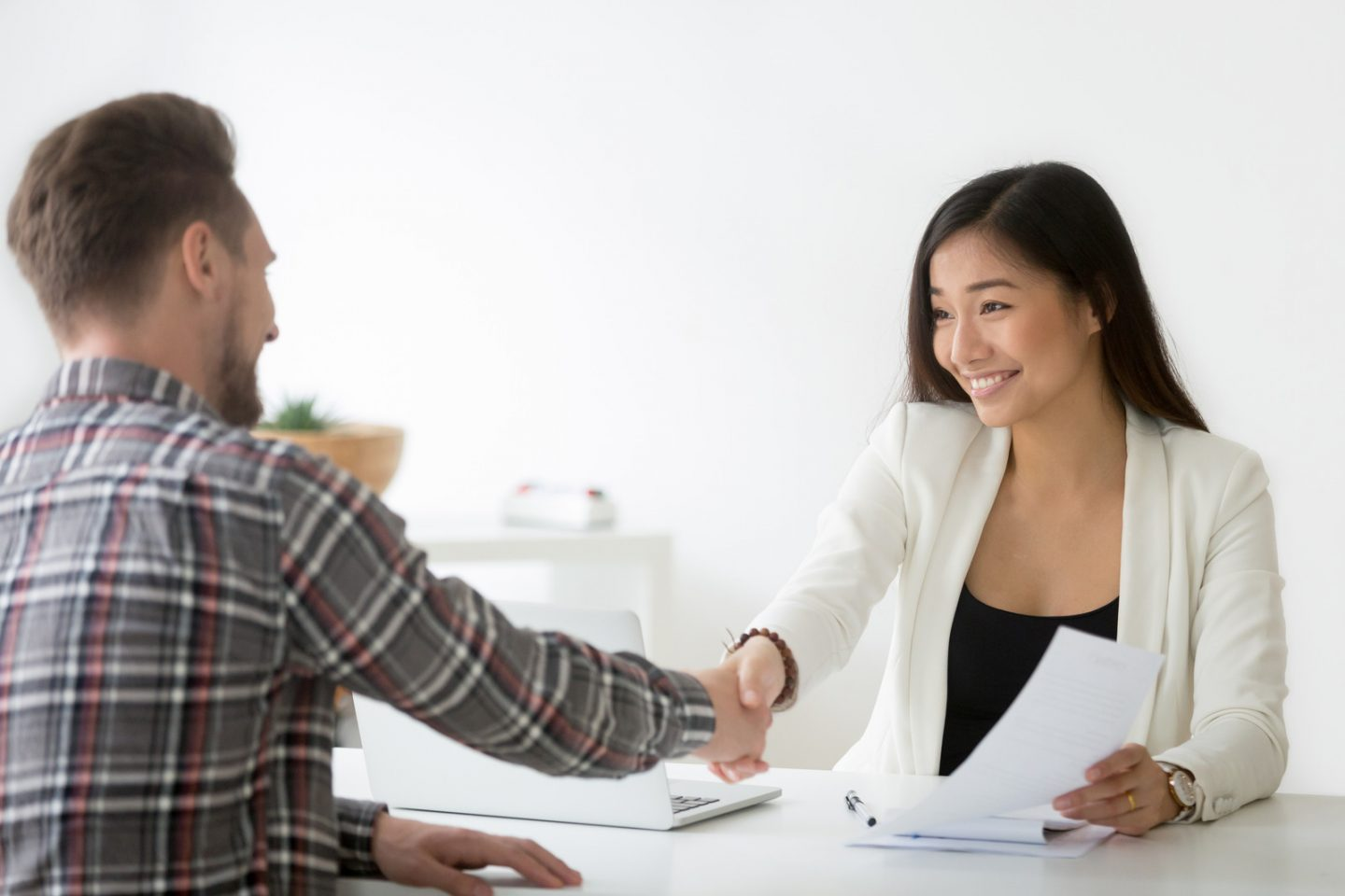 Smiling asian businesswoman handshaking businessman hiring candidate at job interview or signing contract making deal with customer, happy chinese financial advisor and satisfied client shaking hands