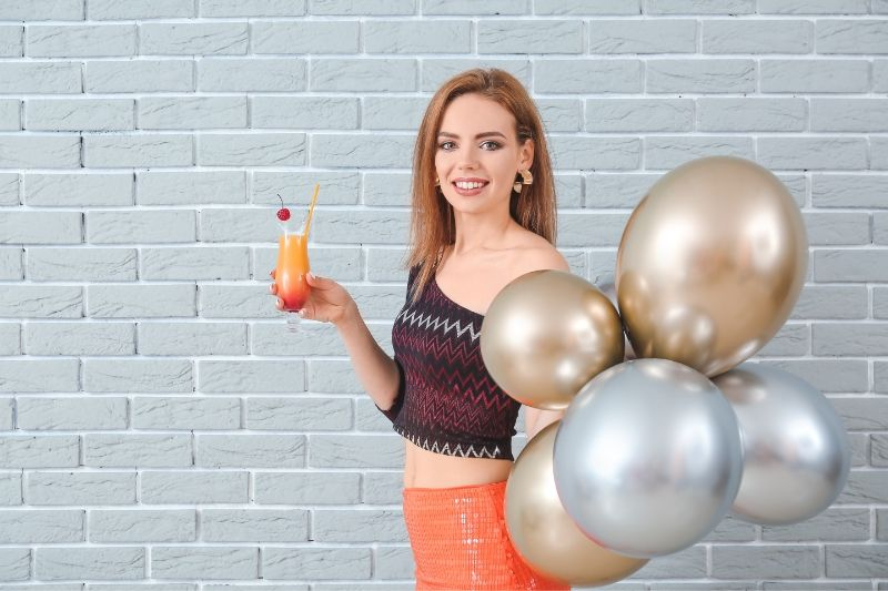 woman with a cocktail and balloons