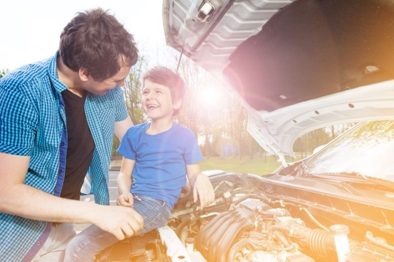 father and son repairing a car