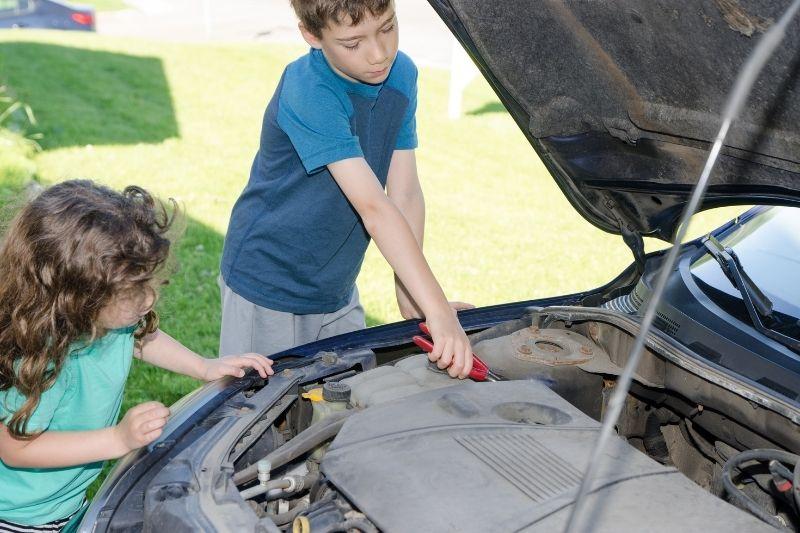 two kids, head under hood, repairing a car