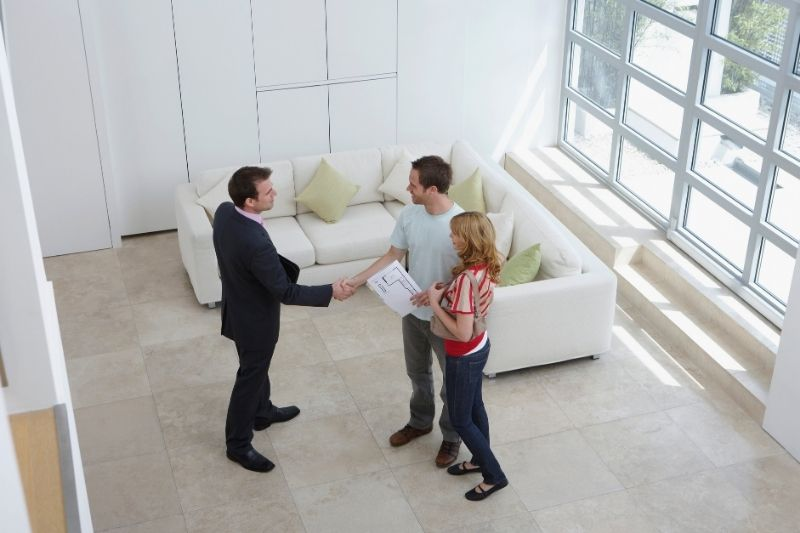 real estate agent with a millennial couple in their new home