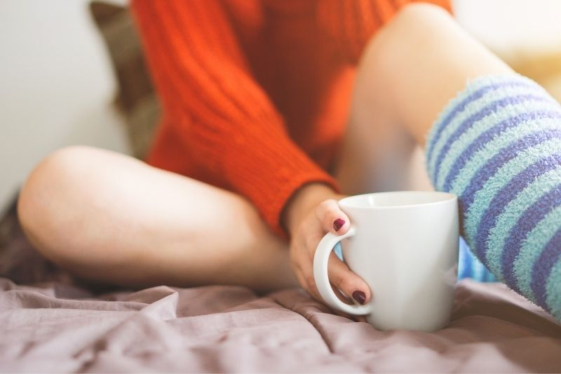 young girl in bed with coffee