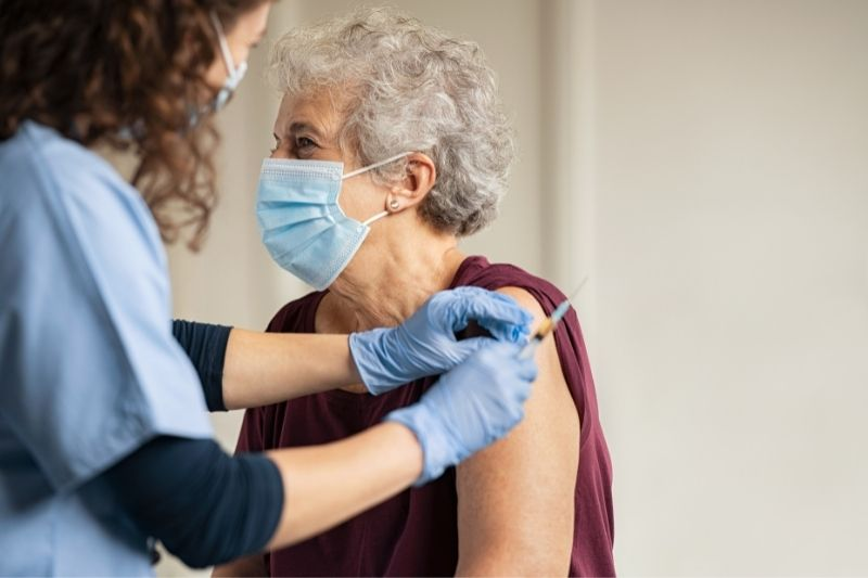 doctor giving an injection to an elderly woman