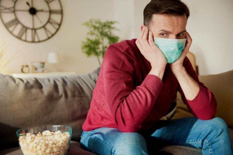 man wearing nose mask sitting at home with popcorn